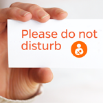 Photo of hand holding business card that says do not disturb